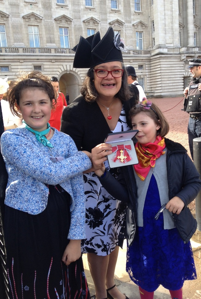 Emily Holzhausen OBE with daughters Isabella and Kristina outside Buckingham Palace
