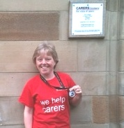 "Rhonda shows off her ""Barrathon"" medal at the Carers Scotland office"